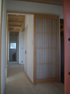 朱色の玄関を開けると格子戸と真っ直ぐのびる廊下がお出迎え